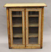 A Victorian bamboo glazed bookcase. 95 cm wide.
