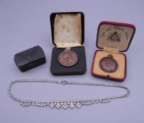 A Winston Churchill medallion, another medallion, a snuff box and a costume jewellery necklace.