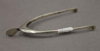 A pair of silver wishbone sugar tongs. 9.5 cm high.