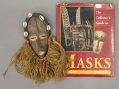 A tribal mask and a Collector's Guide to Masks book. The former 30 cm high.