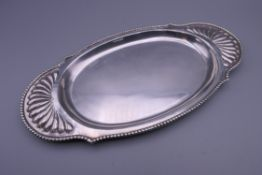 A small silver tray. 23 cm wide.