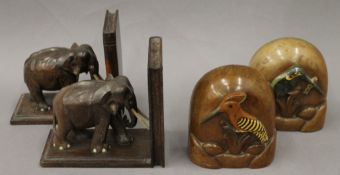 Two pairs of carved wooden bookends, one formed with elephants, the other carved with birds.