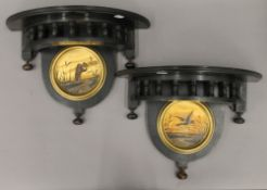 A pair of aesthetic ebonised wall brackets, each with a painted roundel. Each 39.5 cm wide.