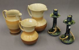 Three Shelley jugs, the largest 23 cm high, and a pair of slipware Arts & Crafts candlesticks.