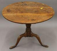 A George III oak tilt top tripod table. 82 cm diameter.