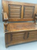An early 20th century carved oak monks bench. 105.5 cm wide.