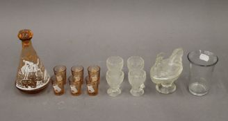 A vintage decanter with hunting scene and six shot glasses, a vintage glass chicken,