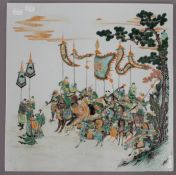 A Chinese famille verte porcelain plaque depicting warriors before battle. 40.5 cm wide.