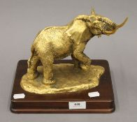 ANTHONY JONES, a gilt bronze model of an elephant mounted on a wooden plinth. 23 cm high.