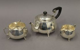 An Arts & Crafts beaten silver three-piece tea set. The teapot 25 cm long. 23.
