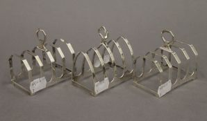 Three silver toast racks. Each approximately 7.5 cm long. 5.2 troy ounces.