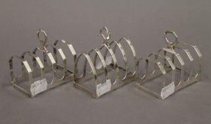 Three silver toast racks. Each approximately 7.5 cm long. 5.2 troy ounces.