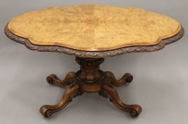 A Victorian burr walnut loo table, the edge carved with shamrocks. Approximately 125 cm long.