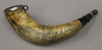 A scrimshaw powder horn decorated with whaling scenes. 37 cm long.