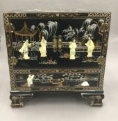 A Chinese lacquered cabinet. 60 cm wide.