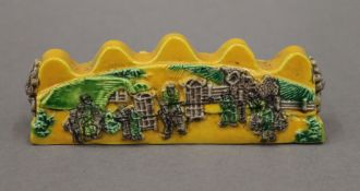 A Chinese yellow porcelain brush rest.