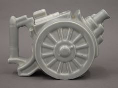 A 1930s tube lines wall plate of a galleon and two vintage teapots, one formed as a canon.