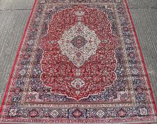 A red ground full pile Kashmir traditional medallion rug. 330 x 240 cm.