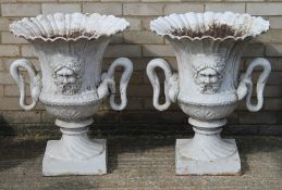 A pair of twin handled cast iron garden urns.