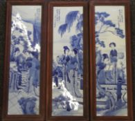 A set of three Chinese framed blue and white porcelain plaques. 80.5 cm high.
