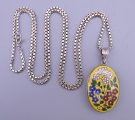 A German silver painted locket on a silver chain. The locket 2.5 cm wide.