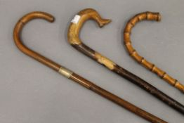 Three vintage walking sticks, one with boot form handle and one by Swaine & Co London.