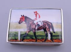 A silver enamel snuff box depicting a horse with jockey up. 5 cm wide.