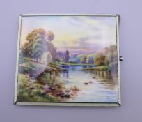 A silver and enamel cigarette box decorated with a river in a county landscape. 8.5 cm wide.