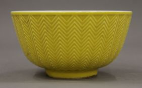 A Chinese porcelain bowl with yellow exterior. 12 cm diameter.