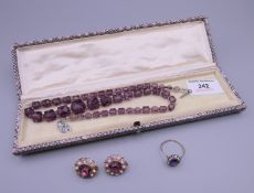 An amethyst set gold ring, together with a dress necklace and a pair of clip on earrings.
