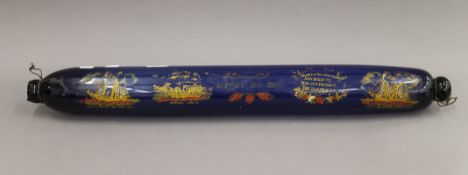 A large Victorian blue glass rolling pin, painted with various ships and verses. 77 cm long.