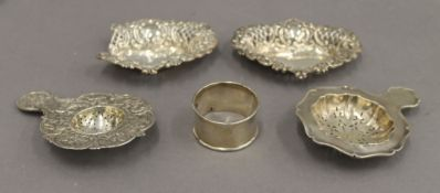 A pair of silver pierced dishes, a napkin ring and two strainers. The former 10 cm wide. 3.
