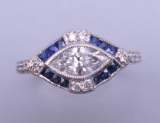 An Art Deco style platinum marquis cut diamond and sapphire ring. Ring size N/O. 4.