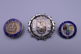 Two antique silver and enamel coin form brooches and a 1914 'On War Service' enamelled lapel badge.