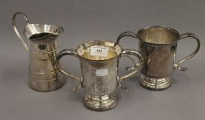 Two silver plated twin handled cups and a jug. The latter 16 cm high.