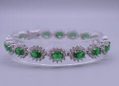A 925 silver and rhodium plated synthetic emerald and diamond bracelet. 18 cm long.