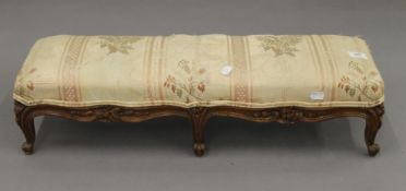 A Victorian upholstered foot stool. 69 cm long.