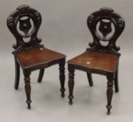 A pair of Victorian mahogany hall chairs. 43.5 cm wide.