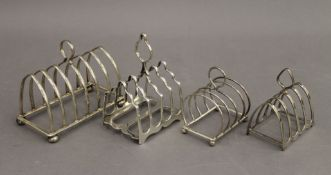Four silver toast racks. The largest 12.5 cm wide. 11.6 troy ounces.