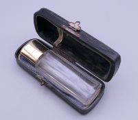 A French 18 ct gold topped scent bottle, cased. 9 cm high.
