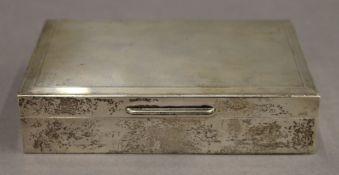 A silver cigarette box. 14.25 cm wide. 12.1 troy ounces total weight.