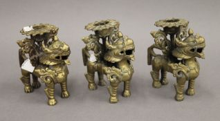 Three Chinese bronze candle holders, each formed as a dog-of-fo. Each 9 cm high.