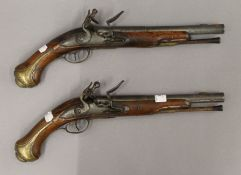 A pair of 19th century Continental flintlock pistols. Each 40 cm long.