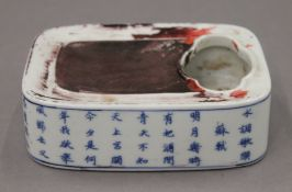A Chinese blue and white porcelain inkstone decorated with calligraphy. 13 cm long.