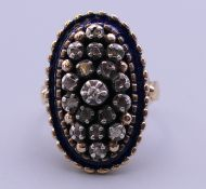 An antique gold diamond and blue enamel oval ring. Ring size M. 8.3 grammes total weight.