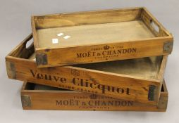 A set of three wooden trays. The largest 56 cm wide.