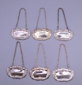 A set of six silver plate decanter labels. Each approximately 6 cm wide.