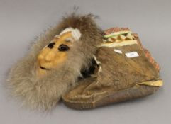 An Inuit seal fur mask and a pair of boots.