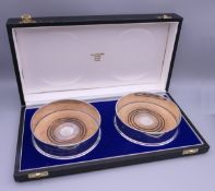 A cased pair of silver coasters. Each 12.5 cm diameter.