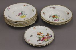 A quantity of Copenhagen porcelain florally decorated plates and dishes.